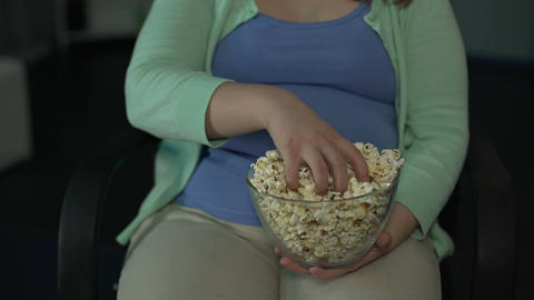 Fat woman taking handful of popcorn from bowl and eating while watching a movie Footage