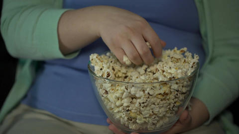 Obese lady taking handful of sweet popcorn and eating it, sedentary lifestyle Footage