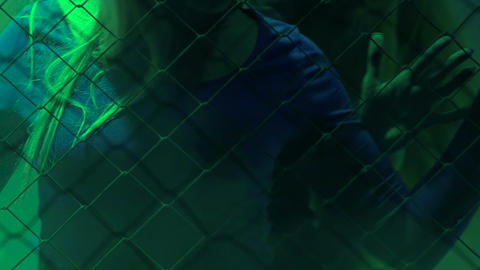 Active young ladies having fun and dancing behind wire mesh fence in nightclub Footage