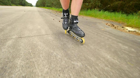 Shuffle inline skating on way in pine forest. Mans legs roller skating on the as Footage