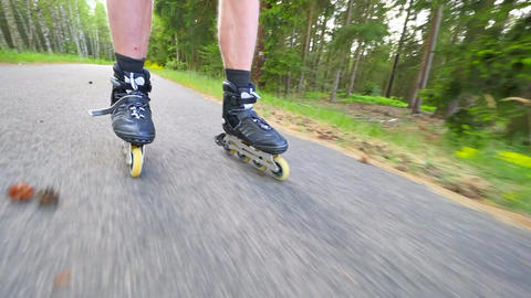 Backwards inline skating and braking on the asphalt. Close up view to move man l Footage