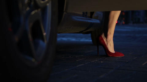 Woman in red heels stepping out of car at night Footage