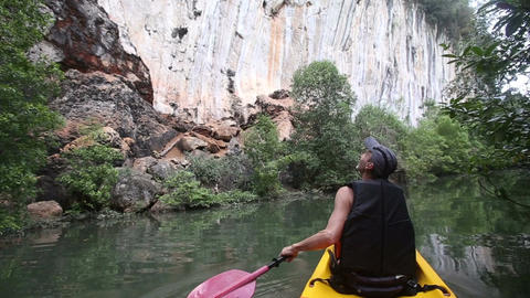 elder strong man rows kayak along river past grey rocks Live Action