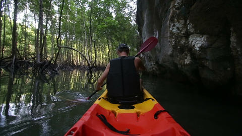 man does sport sailing on kayak past caves Footage