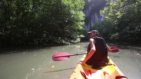 strong elder man rows kayak turns aside and speak Live Action