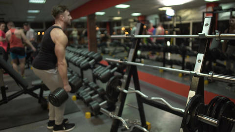 Young male exercising with heavy dumbbells in gym, working for perfect body Footage