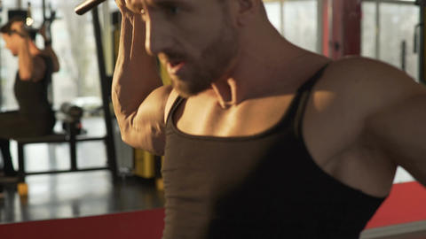 Male athlete doing rear lat pull-downs in gym with big efforts, face strained Live Action