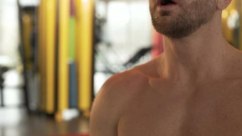Gym member breathing heavily after doing exercise, nodding to his trainer Live Action
