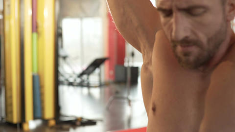 Male practicing rear pull-downs in gym and finishing exercise, his face strained Live Action