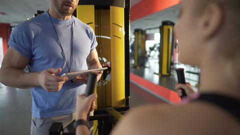 Fitness trainer talking to young woman in the gym, discussing training program Footage