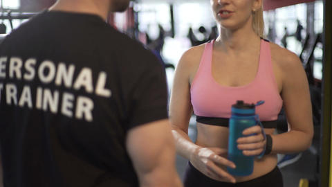 Attractive female client talking to fitness coach after finishing workout Footage