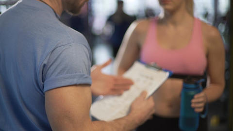 Male and female fitness trainers discussing their work schedules in gym Live Action