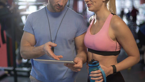 Healthy couple discussing workout plan in gym, defining future fitness goals Footage