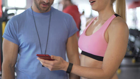 Fit lady showing application tracking her results to personal trainer in gym Footage