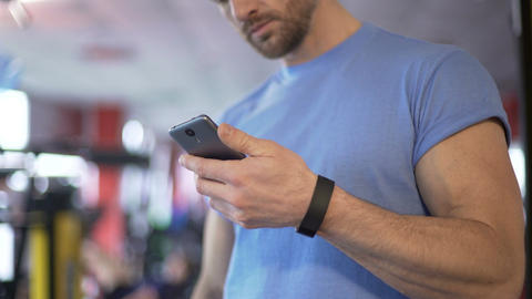 Athlete launching application on smartphone to synchronize with fitness bracelet Footage