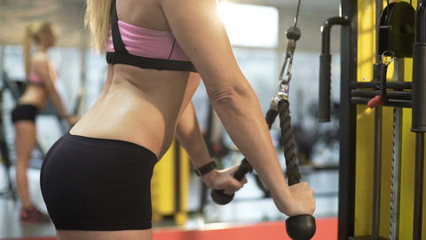 Young blonde woman working out in gym, trying to keep her body at shape Footage