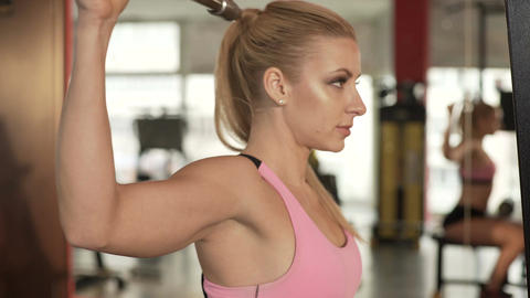 Woman working out hard at gym, bulking up her hands, chest and back muscles Footage