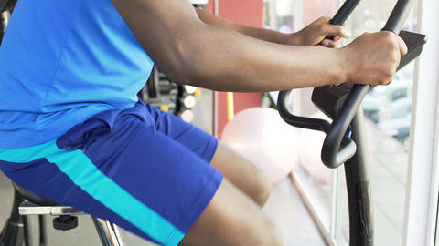 Purposeful Afro-American man riding an exercise bike in the fitness club, sport Footage