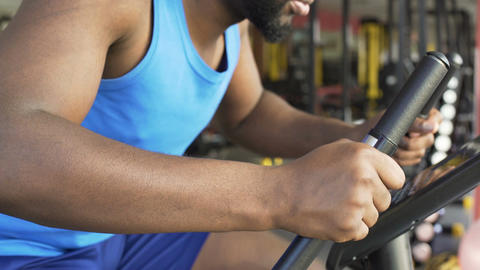 Hard-working male athlete riding stationary bike in fitness club, motivation Footage