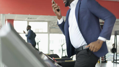 Serious Afro-American male training on treadmill and talking on mobile phone Footage