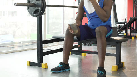 Tiredness after workout, African-American man sitting on training equipment Live Action
