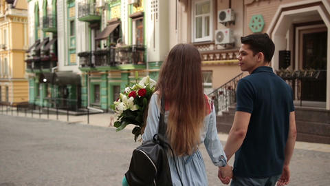 Affectionate couple walking down old city street Footage
