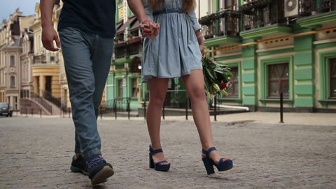 Couple's legs walking down the city street Footage