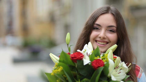 Portrait of smiling young woman smelling flowers Footage