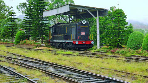 Train passes by the old locomotive on railway station in rural Sri Lanka Footage