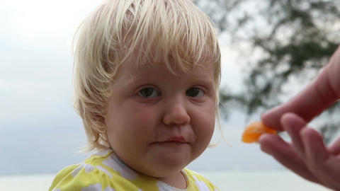 Mother Gives to Little Blonde Daughter Small Piece of Tangerine Footage