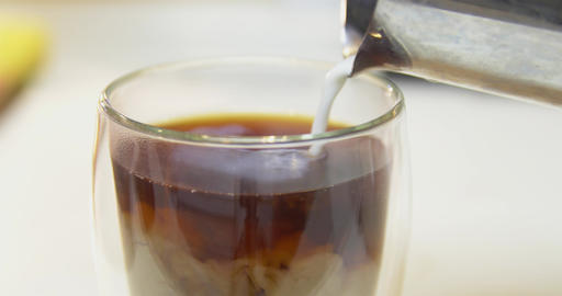 Close up pouring milk into fresh coffee Footage