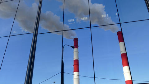 Pipes with a smoke and reflection in a glass building, Russia, Moscow Footage