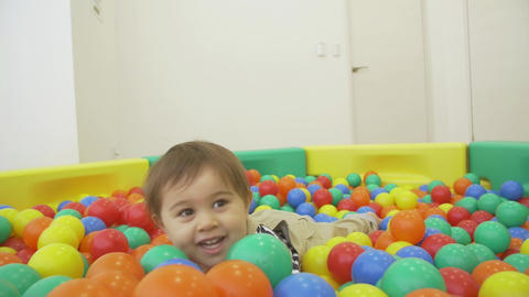 Child jumps in the ball pit slow motion Footage