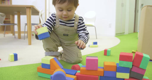 toddler smiles and plays with blocks Footage