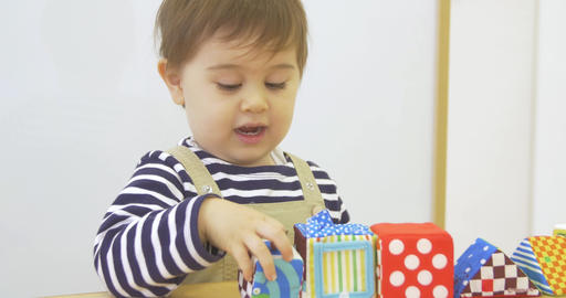 Little boy smiles and plays with blocks Footage