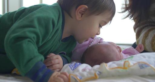 Big brother kisses his new born baby sister ビデオ