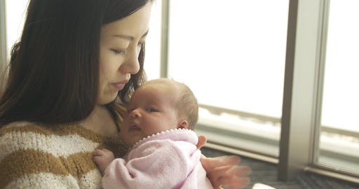 Asian women holding mixed race new born baby ビデオ