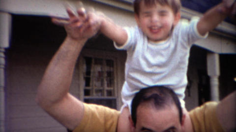 1969: Happy caucasian boy riding on father's shoulders Footage