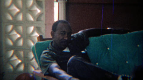1969: Confident African man smoking cigarette outdoor couch party Footage