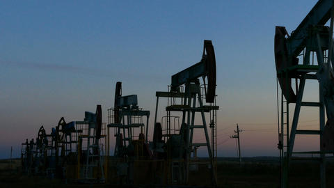 many working oil pumps silhouette in dusk, zoom in Footage