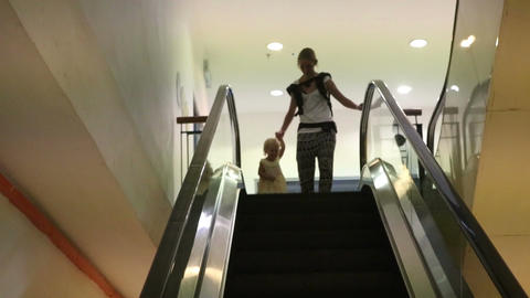 Mother and Daughter Get down the Escalator Footage
