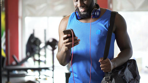 Handsome athletic man reading message on mobile phone with happy smile on face Live Action