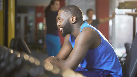 Handsome self-confident man looking at ladies in gym, smiling and flirting Footage