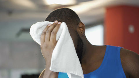 Attractive male wiping face with towel, looking seductively at camera, flirt Live Action