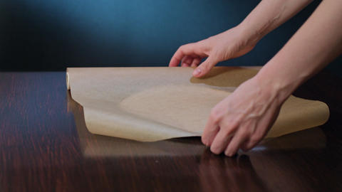 Cook Cutting a Section of Baking Paper with Scissors Footage