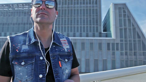 Modern architecture and City lifestyle Man earing music with smartphone Footage