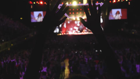 Anonymous woman with arms up in christian concert