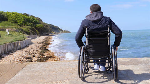 Back of disabled man in wheelchair at beach slow motion