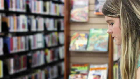 Attractive blonde at library reading a book in an aisle - Angle 1 Footage