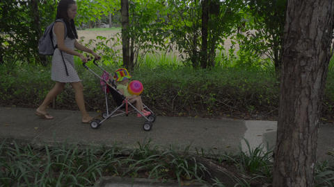 Woman walking with child in park of hotel Live Action
